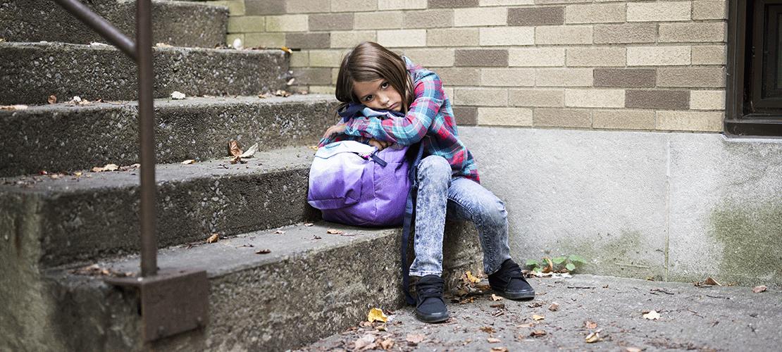 Ein kleines Mädchen sitzt auf der ersten Stufe eine Steintreppe. Sie lenht an die Wand. Den Oberkörper hat sie auf ihre Tasche gelehnt. Sie blickt sehr traurig in die Kamera.