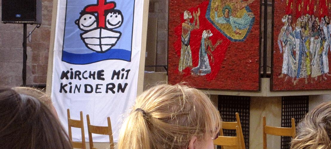 In einer Kirche schauen drei Kinder nach vorne zur Kanzel und zum Altarraum. Lins neben der Kanzel steht ein Rollscreen. Darauf ist ein Schriftzug: Kirche mit Kindern. Darüber zeigt ein handgemaltes Bild ein Boot von vorne. Darin zwei fröhliche Kindergesichter, links und rechts neben dem Mast des Schiffes. Der Mast hat eine Kreuzform.