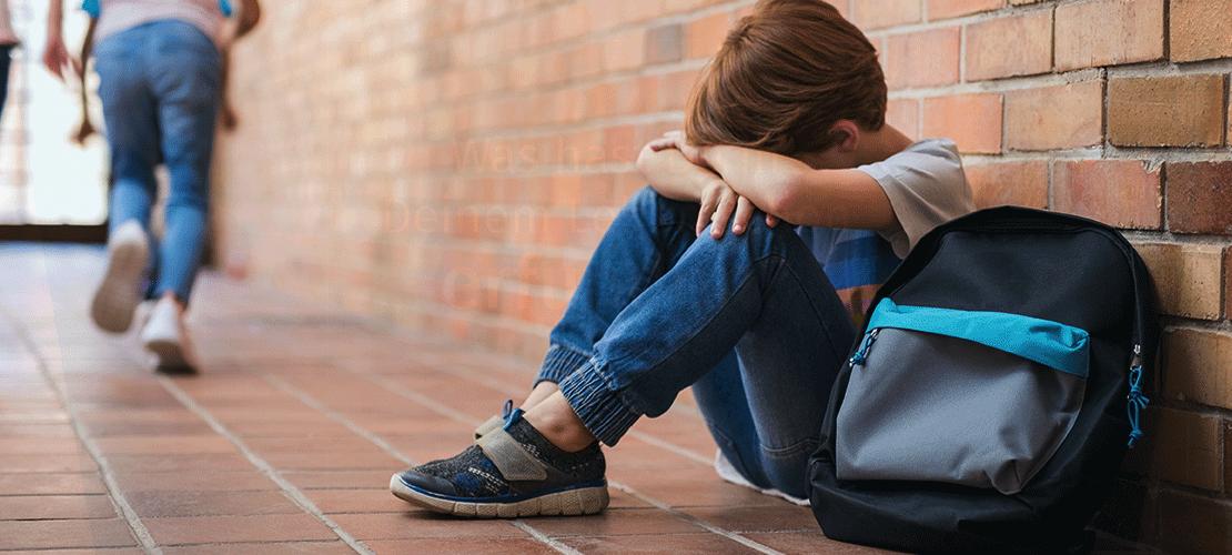 Auf einem Flur in einer Schule sitzt ein kleiner Junge neben seiner Schultasche mit dem Rücken an einer Backsteinwand. Er hat die Knie angezogen, die Arme über den Knien verschränkt. Den Kopf hat er auf Knie und Arme gelegt. Im Hintergrund laufen andere Kinder vor ihm davon.