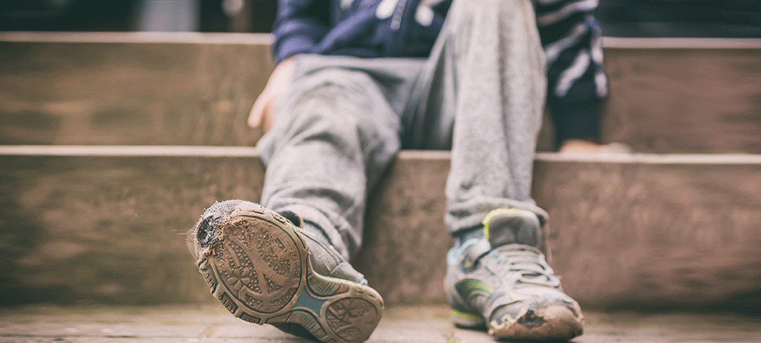 Auf einer Treppenstufe sitzt ein Jugendlicher. Er streckt die Beine aus. Die Schuhsohlen sind löchrig. Die Hosen sehr einfach. Sie sehen mitgenommen aus.