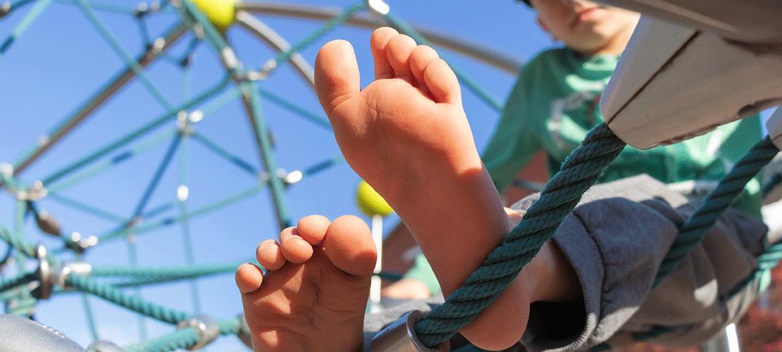 Von unten schaut man in ein großes Klettergerüst aus einem Seil-Netz auf einem Kinderspielplatz. Ein Junge sitzt in dem Netz. Mit seinen nackten Füßen, die direkt vor der Kamera sind, stützt er sich auf einem Seil ab.